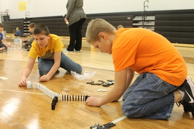 Students setting up dominoes for STEM project